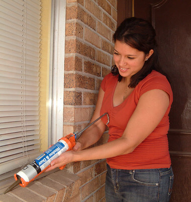woman caulking window